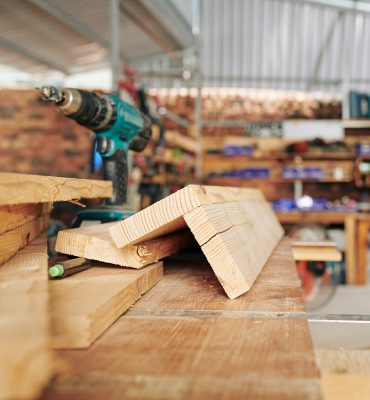 Drill and connected wooden planks on workbench in furniture manufacture, selected focus