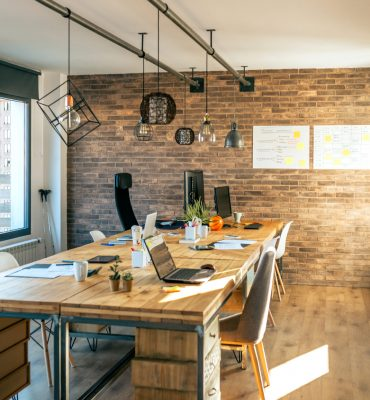Interior of industrial style coworking office with various workplaces